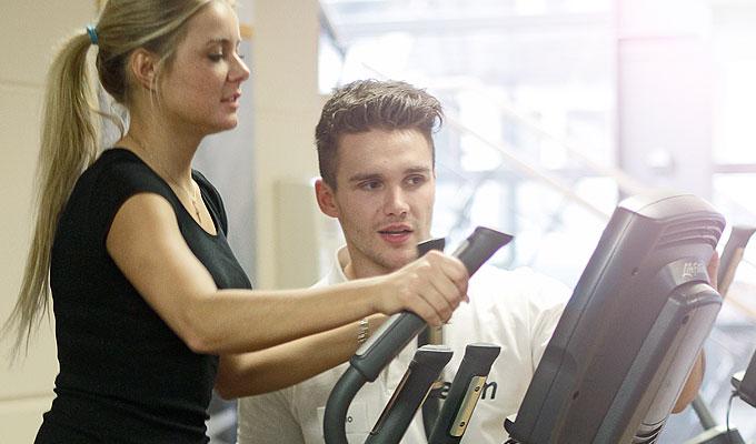 Junge Frau trainiert am Cardiogerät